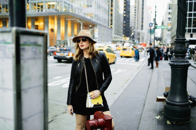Girl in beige hat and sunglasses stands on the street of ny