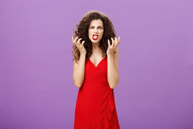 Girl being pissed, sicked and tired with irritating woman on party squeezing fists in rage and annoyance grimacing making disappointed, bothered expression talkign about pain in ass over purple wall.