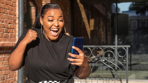 Девушка в шоке, глядя на свой телефон с копией пространства