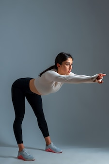 Girl bending body forward with outstretched arms on grey wall