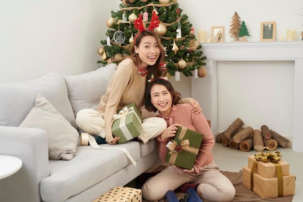 一緒にクリスマスを祝う女の子の親友。家で贈り物を交換し、抱きしめていることに感謝している若い女性。クリスマスの概念の友情が大好きです。