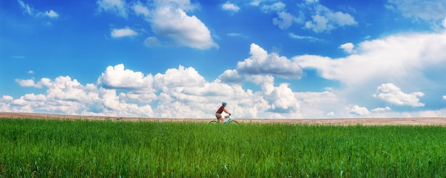 Girl on a bicycle in a green field agains beautiful blue sky with white clouds. panorama. landscape. freedom concept.