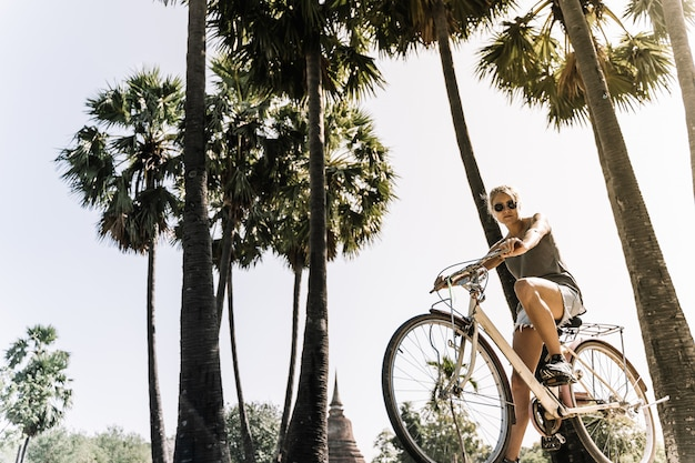 Girl on bicycle on a summer day, in a tropical site with palm trees and sun rays in the . vintage style
