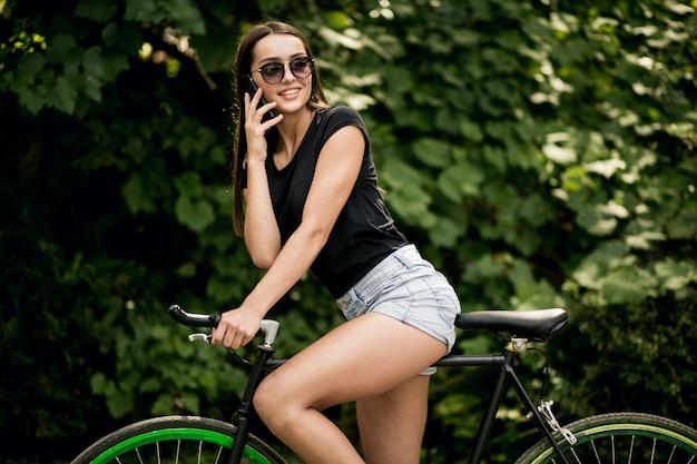 Ragazza su una bicicletta con il telefono