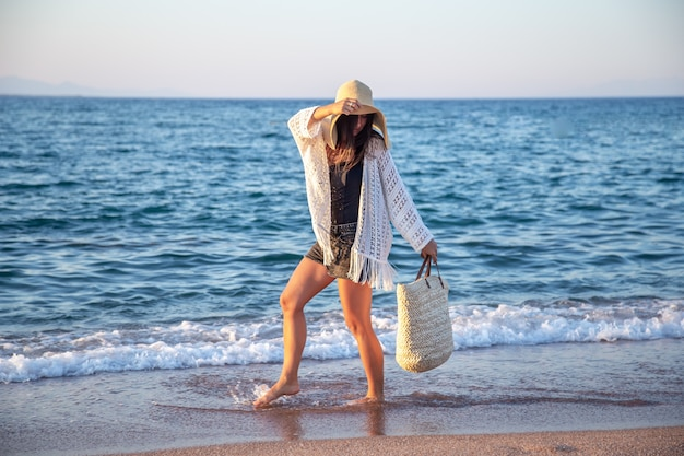 A girl in a big hat with a wicker bag walks on the seashore. summer vacation concept.