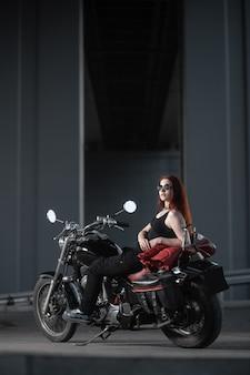Девушка-байкер сексуально позирует на мотоцикле в ночном городе