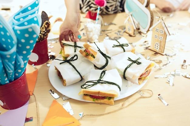 女の子の誕生日の装飾。ケーキ、飲み物、パーティーガジェットを上から見たピンクのテーブルセッティング。