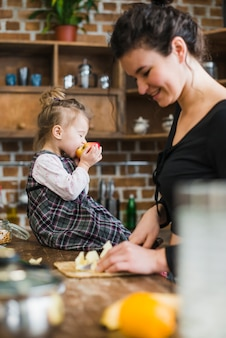 Girl biting apple near cooking mother