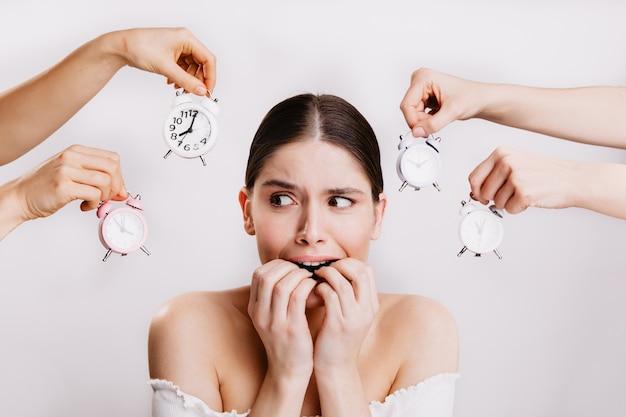 恐怖で指を噛む少女。恐怖の女性は、時計を持っている手の壁に向かってポーズをとる。