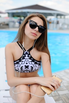 Girl in a black bathing suit sitting on a pool background and listens to music in white headphones.