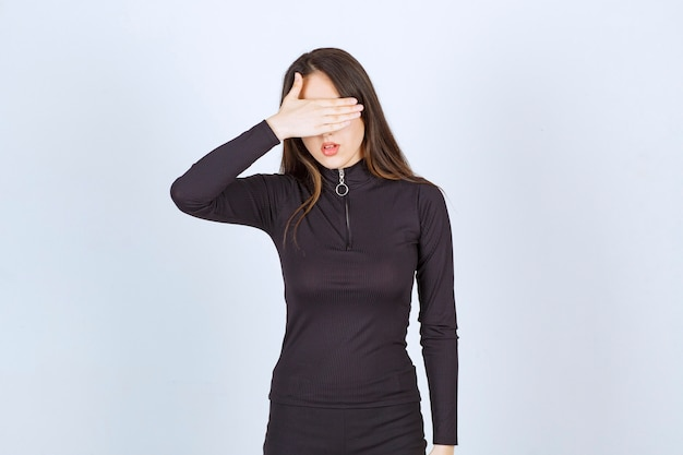Girl in black clothes covering her face or eyes.