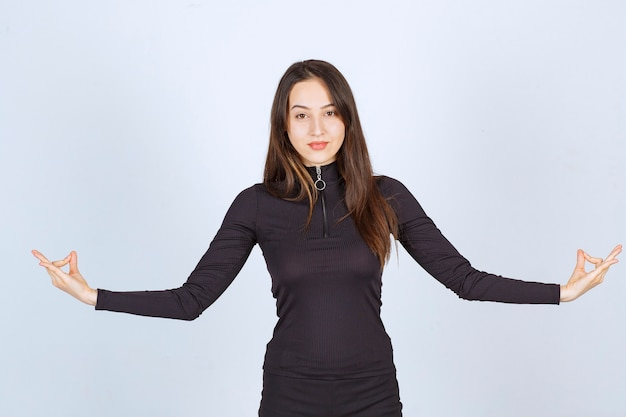 Girl in black clothes doing meditation.