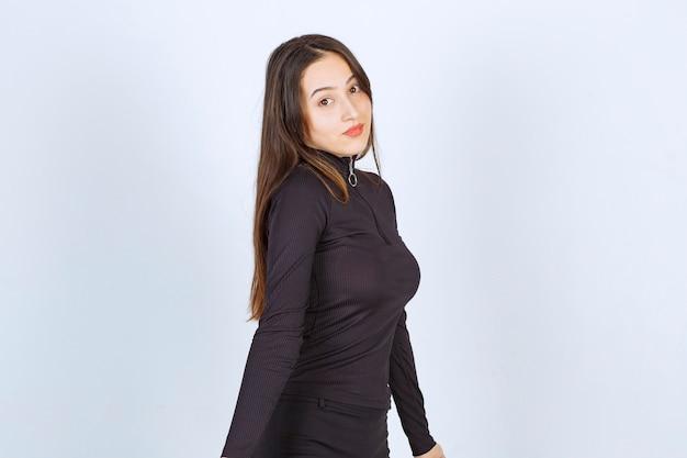 Ragazza in vestiti neri che danno pose professionali e neutre senza reazione.