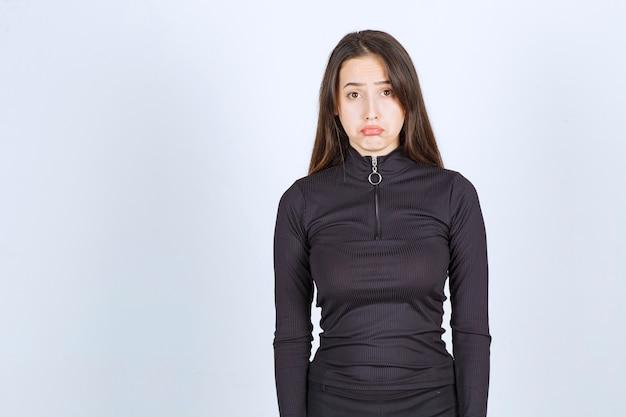 La ragazza in abiti neri sembra triste e depressa.