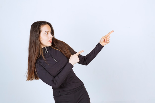 Girl in black clothes pointing at something on the right.