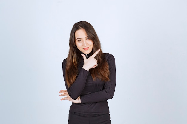 Girl in black clothes pointing at something up.