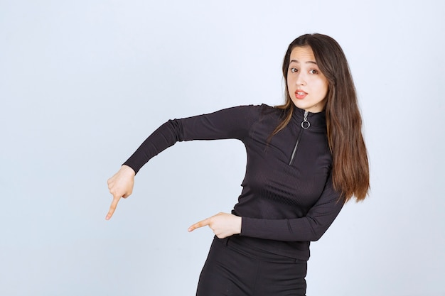 Girl in black clothes pointing below.
