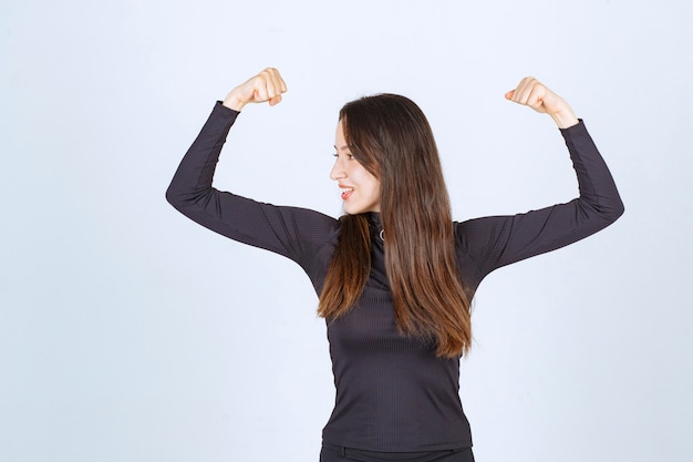 Girl in black clothes showing her fist and arm muscles.