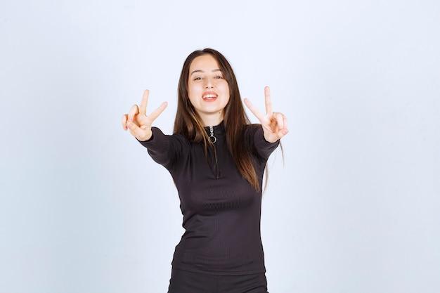Ragazza in vestiti neri che mostrano il segno di amicizia e di pace.