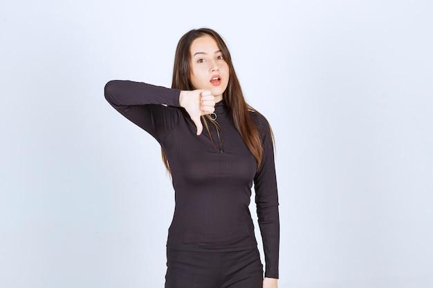 Ragazza in vestiti neri che mostrano il segno del pollice verso il basso.