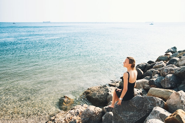 Girl in black dress on background of sea or lake woman relaxed over sea on the big wild stone beach