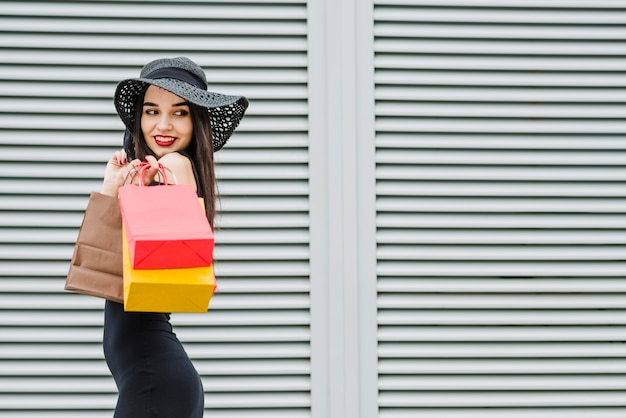 Girl in black dress carrying shopping bags