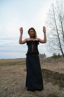 A girl in a black dress in the forest.the girl is a witch in a black corset.dark forest with dry twigs