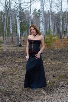 A girl in a black dress in the forest.the girl is a witch in a black corset.