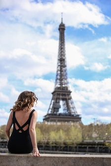 Girl in a black dress from the back and looks at eiffel tower in paris in summer