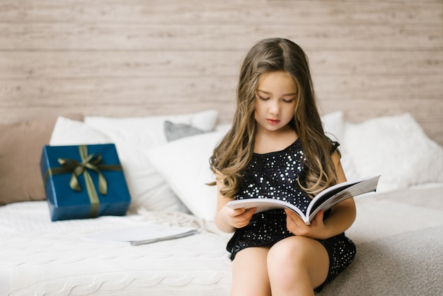 A girl in a black dress is holding a magazine and reading it, sitting on the bed, on which lies a blue gift box with a green bow