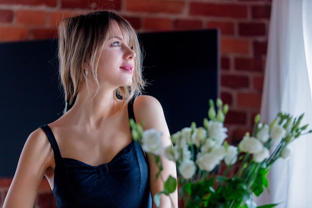 Girl in a black dress is holding white roses before putting them in a vase