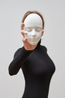 Girl in a black jumper hold plaster gypsum sculpture instead of face on a white wall, place for text. concept the masks we wear.