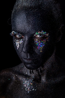 Girl in black makeup with sparkles