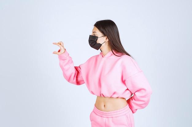 Ragazza in maschera nera che mostra la quantità o la dimensione di un prodotto.