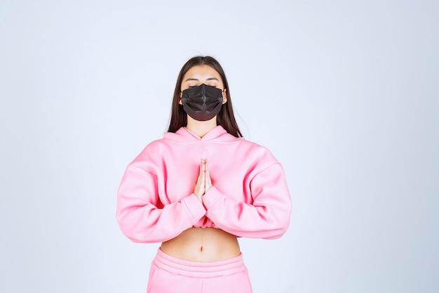Ragazza in maschera nera che unisce le sue mani e che prega.