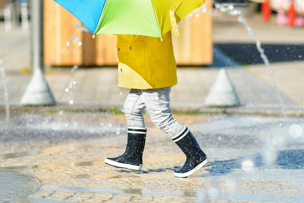 Girl in black rubber boots running through the puddles