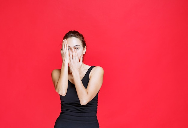 Girl in black shirt covering one eye and looking with another. high quality photo