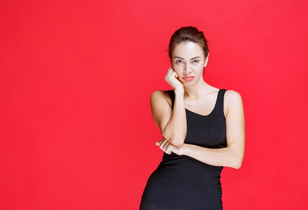 Ragazza in camicia nera che si sente positiva e sorride dolcemente. foto di alta qualità