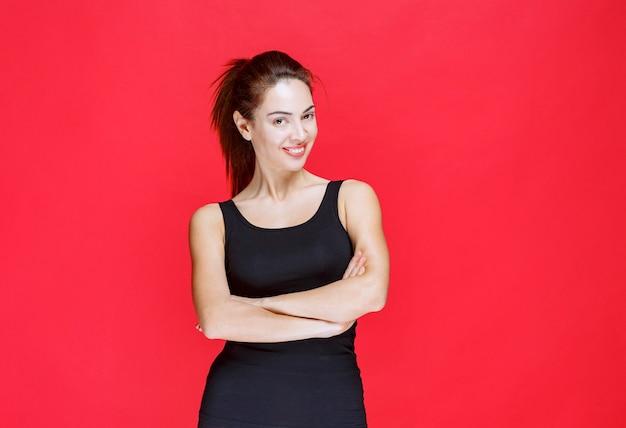 Ragazza in camicia nera che dà pose seducenti e accattivanti. foto di alta qualità