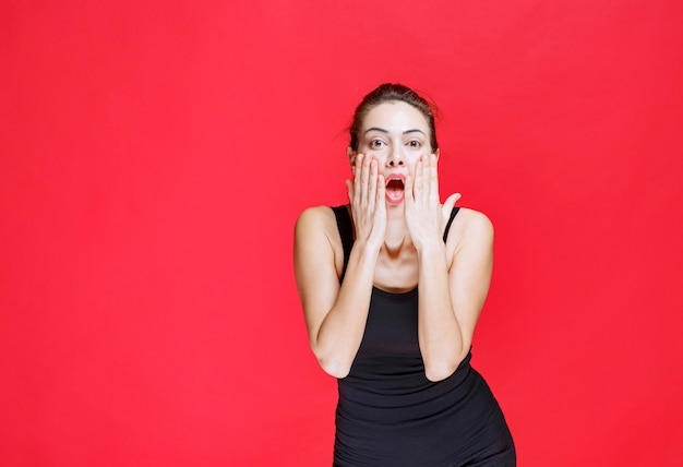 Girl in black shirt holding her head and reacting as a fool. high quality photo
