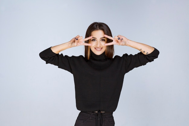 Girl in black shirt looking across her fingers. high quality photo