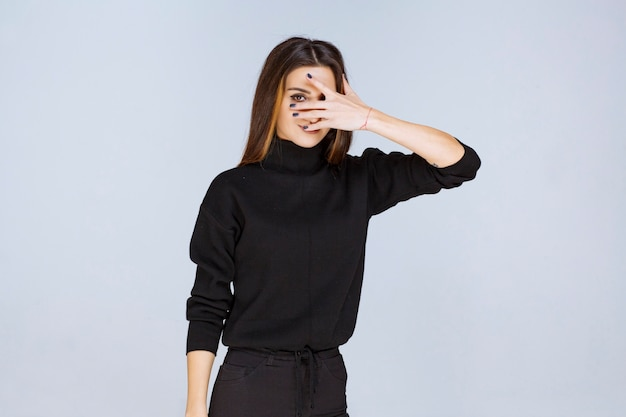 Girl in black shirt looking through her fingers. high quality photo