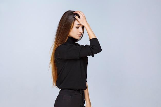 La ragazza in camicia nera sembra esausta e assonnata. foto di alta qualità