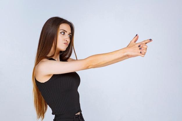 Ragazza in camicia nera che fa il segno della pistola della mano.