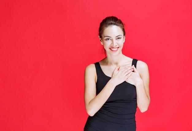 Ragazza in camicia nera che indica se stessa. foto di alta qualità