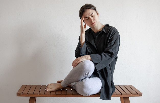 A girl in a black shirt sits on a bench and suffers from mental or physical pain.