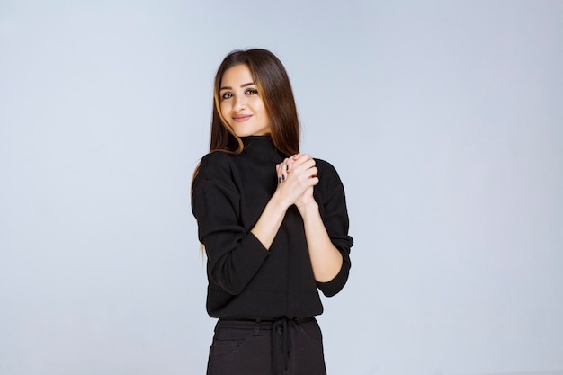 Girl in black shirt uniting her hands and praying. high quality photo