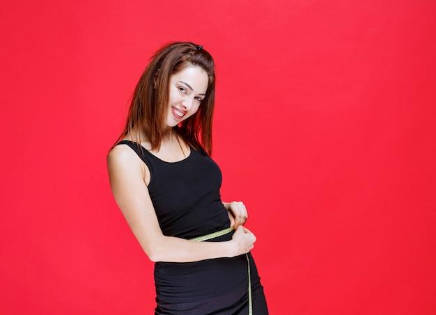 Girl in black singlet holding a measuring tape, measuring her waist and feeling good.