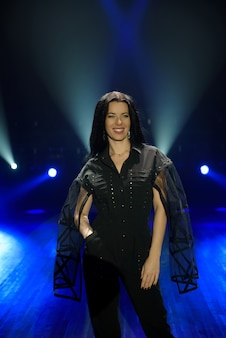 Girl in black suit performing on stage with bright blue background.