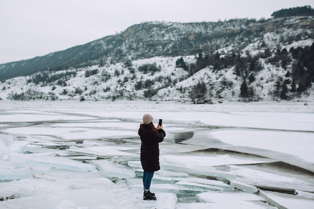 A girl in a black winter jacket, taking photos of winter landscape of frozen river with ice floes.